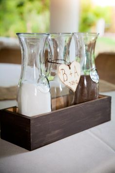 Unity sand in glass milk containers and wooden engraved heart. Great for a rustic wedding!