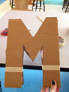 Step 1: Cut out letter in card board Step 2: Support letter with dixie cups   Step 3: Fully tape edges   Step 4: Make a glue/water soluti...