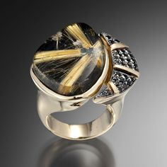 Midnight Star Rutilated Quartz Ring is dark and enchanting. This unique ring design features a star burst slice of rutilated quartz with black diamond accents set in yellow gold.