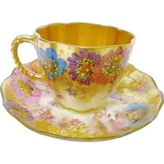 Royal Crown Derby china, England. Exquisite gold tea cup and saucer. Embellished with hand painted mauve, blue pink flowers with Hand applied