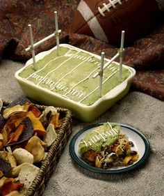 guacamole dip displayed like playing field with lollipop sticks as goal post ~ sour cream as field markers