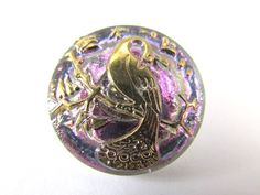 A gorgeous peacock 22mm button with an AB aurora borealis finish over lavender with a gold peacock flowing gracefully over the colors. These buttons are hand made in Czechoslovakia by pressing multipl
