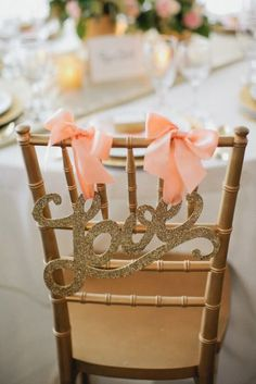 A gold glitter Love sign tied with bows.  Photo Source: loverly #chairdecor #gold