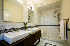 Master bathroom with walnut double vanity, white vessel sinks, brushed nickel wall-mount faucets, ...