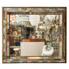 For Sale on 1stdibs - A large-scale, Hollywood Regency style wall mirror, with mirrored panel shadow box frame, bordered by reverse hand-painted flowers and acanthus leaves,