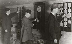Anonymous | Prikklok in een fabriek, Anonymous, 1920 - 1935 | Twee mannen met bolhoed en een jongeman met pet/hoed zijn bezig zich via een prikklok aan te melden op hun werk. Het is vijf voor acht.