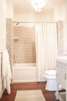 """Paint Colors: BM Valley Forge Tan – Base for the vanity and """"weathered"""" wood; BM Soft Chamois – Top coat for weathered wood; BM Maritime White – Walls; Olympic Granite (diluted with clear glaze) – Top coat for vanity  Materials: Mannington Heritage Hickory flooring; Winchester Tile Company hand-glazed tiles in Canvas; White standing stone """"tiles""""; 3/4″ travertine mosaic tiles for vanity counter; Kohler Archer tub; Kohler Archer sink; Capiz hanging pendant from World Market"""