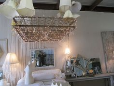 Salvaged metal bed frame springs and lampshades repurposed into giant light fixture chandelier installation for vintage cottage style home decor or retail store display