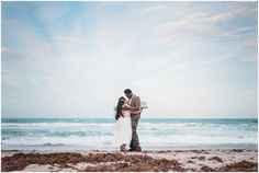 Couple holding each other with ocean in background during Cocoa Beach Wedding