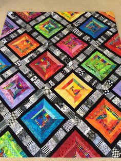My Bright Scrappy Patchwork Quilt.  Made with a strip of 3 inch black and white scraps on the diagonal, followed by 1 1/2 inch black strip flipped on each side. I then added varying sizes (1/2 inch - 2 inch) bright strips.  The block was 10 inches finished.  #Strippy quilts, #scrappy quilts, #string quilts. Marie Larsen Caloundra Qld Australia.