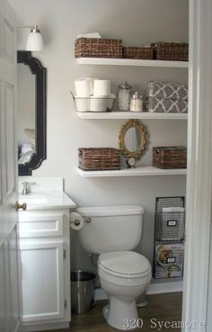 shelves over toilet--basket for toilet paper, basket for lotions / toiletries / make-up, seashells, candles,and plaque that says Be-you-tiful