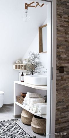 A beautiful Scandinavian style bathroom. I love the sink and the unique light fixture.