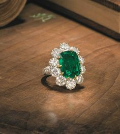 An emerald and diamond cluster ring featuring a cushion-shaped, 10.09-carat emerald surrounded by brilliant cut diamonds