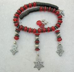 """by Sandra Francour   Old red glass African trade beads called """"vaseline"""" beads. (Originally Bohemian made, these beads were widely traded mid to late 1800s) are combined with an antique Ethiopian silver Star of David and two new Ethiopian Coptic crosses.  the back heishi is coconut and all the silver beads and clasp are sterling silver   255$"""