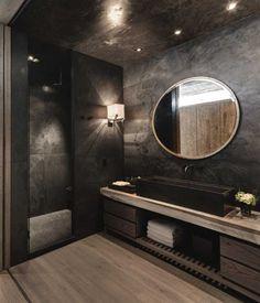 salle de bains sombre et glamour aménagée avec un meuble sous-vaque en bois massif et un parquet en bois