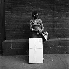 Woman standing with a bag and a big box waiting.