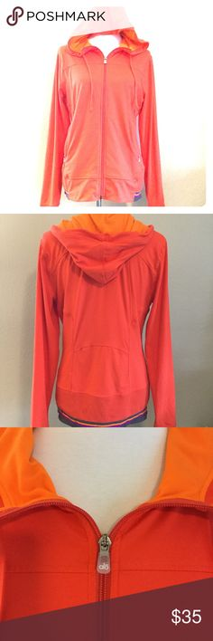 ALO Cool Fit SZ L Track Yoga  Hoodie Jacket Orange Alo Cool Fit women's size large orange full zip hoodie track jacket. Jacket is great for layering - yoga, or just running around on a casual day. Zippered pockets and a fun striped design on sleeve and bottom hems. Great pre-owned condition with no flaws. Fast shipping - same or next business day.  Measurements Armpit to armpit: 20 inches Length: 26 inches ALO Yoga Jackets & Coats