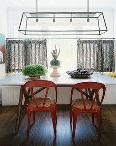 Love the seats on these red chairs!    Cafe Curtains Photo - An iron-and-glass chandelier suspended above red chairs and a marble table