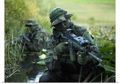 U.S. Navy SEALs cross through a stream during combat operations