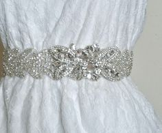 "BEATRICE DELUX is decadent beaded rhinestone ribbon sash. This exquisite sash countless clear crystals in silver settings and glass beads in an intricate scalloped design. Featuring a stunning hand embellished side piece with faux pearls imported from Japan.    - Measures 2"" wide  - Crystal embellishments measures 18"" across  - Available in 1.5"" ivory or white"