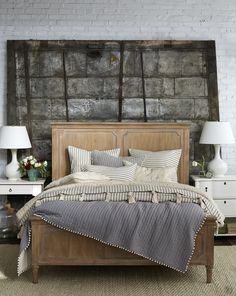 Industrial loft-style bedroom with ticking stripe bedding and pom pom quilt