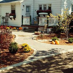 Yard with multiple ground covers - wood deck, stone pavers, bark mulch in planter beds and gravel pathways