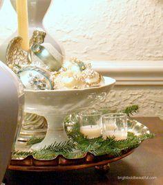 We love Holiday Vignettes using fresh evergreens, ornaments and votives brightboldbeautiful.com