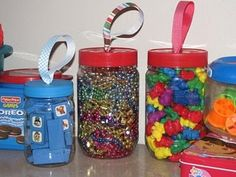 Punch a hole in the lid of a plastic jar and string a ribbon through it. Knot it on both sides of the lid. Great storage containers for manipulatives and the handles allow them to be carried around.