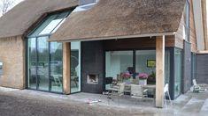 Een eigentijdse woning die echt in het oogt springt door de toegepaste materialen. De woning heeft een rieten kap met een doorlopende pui in de gevel en dak