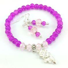 Komplet biżuteriidamskiej wykonany ręcznie. Kolczyki i bransoletkaz koralików szklanychkulek w odcieniu fuksji, różowych kryształków szlifowanych oraz elementów w kolorze srebrnym. Dodatkowozawieszka charms w kształcie róży.