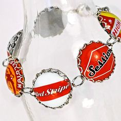 Use long necked bottles or jars with fatter bottoms as display holders; like with this bottle cap bracelet.