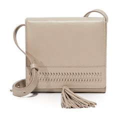 La boite tassel cross body bag by GRACE ATELIER DE LUX. This boxy GRACE ATELIER DE LUX cross body bag is accented with woven trim and a large tassel. Magnetic top flap and s...