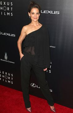 Katie Holmes con total look de Michael Kors con blusa asimétrica con volantes y transparencias en negro, pantalones en el mismo color y zapatos estampados.
