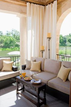 Don't be afraid to mix different types of porch furniture and accessories. Soft curtains, wicker furniture and a rich wooden coffee table come together in lavish harmony.