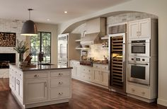 "Contemporary Kitchen with Fossil Brown Quartz, Hardwood floors, Sub-Zero 30"" Built-In Column Wine Storage, European Cabinets"