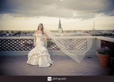 Veil blowing in the wind while bride standing on the rooftop of the Omni Hotel overlooking New Orleans skyline.