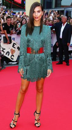 Emily Ratajkowski wears a beaded Balmain dress with a red belt and Giuseppe Zanotti suede and metal strappy sandals