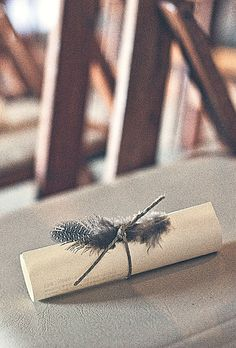 Scrolled ceremony programs embellished with twine and guinea feathers. Photo by Chennergy.