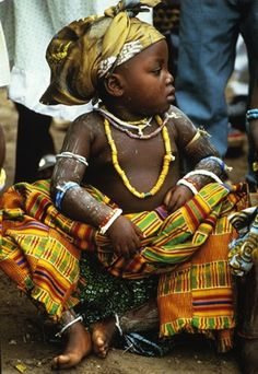 """Small Krobo Girl, Sitting by Angela Fisher and Carol Beckwith.""""Dressed in her family's finery, the little girl wears handwoven silk keente cloth and valuable old glass beads to enhance her status at the Outdooring ceremony""""(please do not repin without including photographer's credits)"""