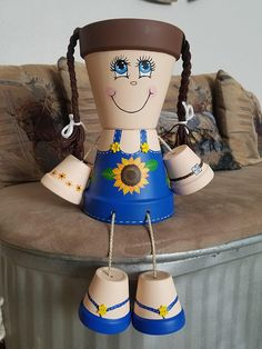 Sunflower Clay Pot People. She is made with two 6 Terra cotta clay pots for her head & body, and four 3 Terra cotta clay pots for her hands & feet. She is hand painted using high quality outdoor paint, then sprayed with a sealer to protect her. Her hair is made from craft cord. She is