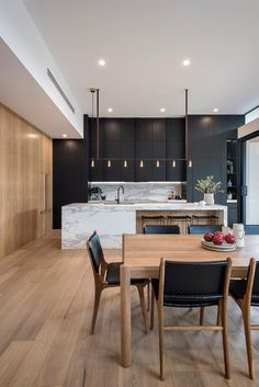 Black cabinets + Marble countertops + Waterfall countertop + Wooden table + Black accent chairs + Stool seating + Wood wall | Georgie Shepherd