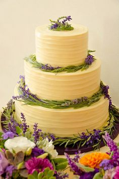 Locally grown lavender, rosemary and salvia encircle the layers of this wedding cake. Designed by Local Color Flowers www.locoflo.com