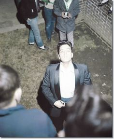 Elvis Presley at the gates of Graceland - March 12, 1960. Elvis Presley is playing host to the Holiday on Ice company today at his home. Buses were to leave the Hotel Claridge at 2:30, carrying the entire company to Graceland to spend the afternoon.