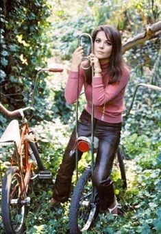 Natalie Woods sits on a bike, backwards.