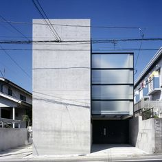 This rectangular concrete block with a volume protruding from its side is a family home in Tokyo by Japanese studio Apollo Architects & Associates.