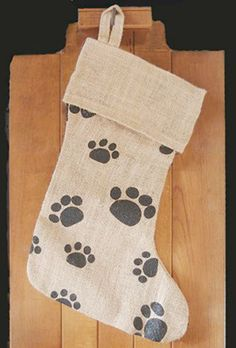 """HI-157B/$12.95: Natural burlap stocking with black paw prints. Measures 12"""" wide (at the bottom); 17 in. tall; 2-inch hanging loop. Folded top cuff is 8"""" wide x 4"""" long. Perfect spot to print your pet's name!"""