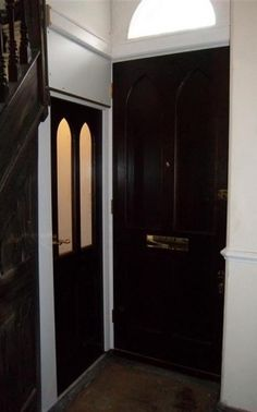 Victorian Gothic internal door in dark stained wood. Brass door furniture