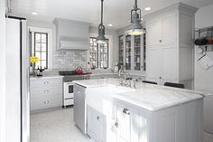 New England Design Works - kitchens - industrial yoke pendant, industrial pendant lighting, beadboard kitchen ceilings, beadboard ceilings, farm sink in kitchen island, kitchen island with apron sink, bridge sink faucet, gray shaker kitchen, gray shaker cabinets, gray cabinetry, white and gray marble counters, marble subway tile, marble subway backsplash, white stainless steel range, paneled range hood, gray paneled kitchen hood, steel framed windows, steel kitchen windows, built in kitchen…