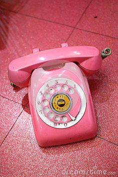 A pink old retro telephone on a floor.