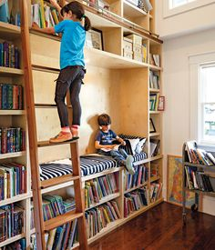 A former  closet was transformed into a double-height library, complete with a reading nook and a rolling ladder from Spiral  Stairs of A...